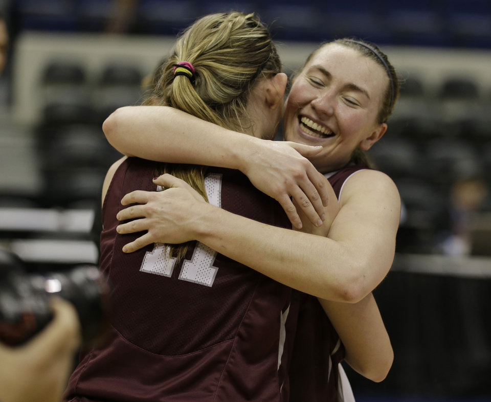 Photo - Fordham guard Abigail Corning, right, hugs teammate forward Emily Tapio (11) after winning the A10 Women's basketball championship game against Dayton in Richmond, Va., Sunday, March 9, 2014. Fordham defeated Dayton 63-51. (AP Photo/Steve Helber)