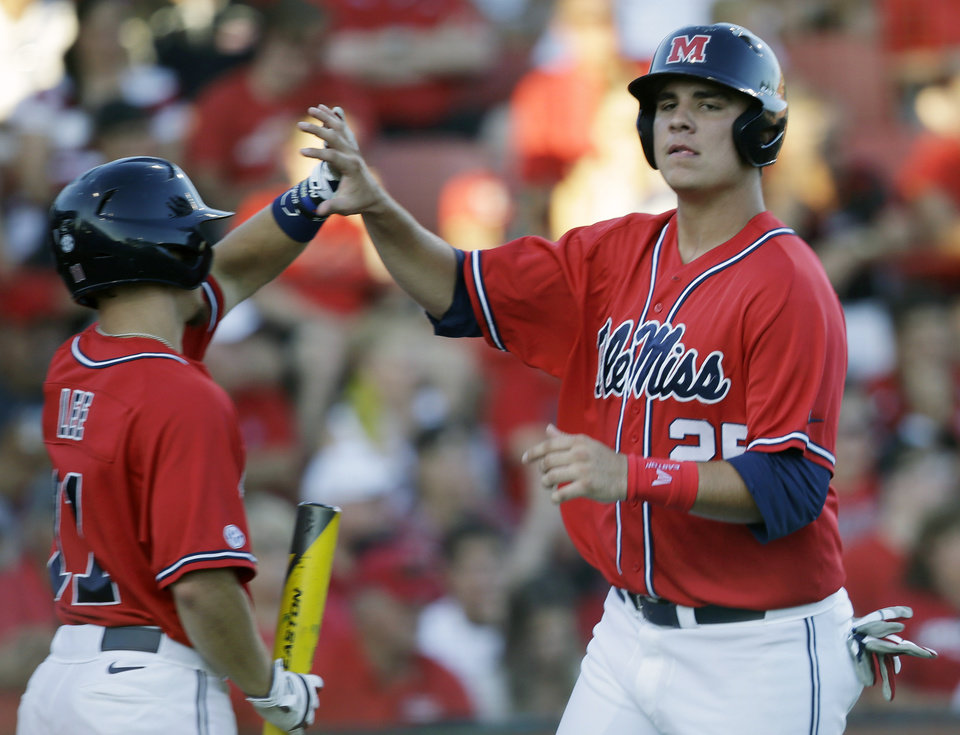 Photo - Mississippi's Colby Bortles (25) is greeted by Braxton Lee after scoring a run in the second inning of an NCAA college baseball tournament super regional game in Lafayette, La., Saturday, June 7, 2014. (AP Photo/Gerald Herbert)