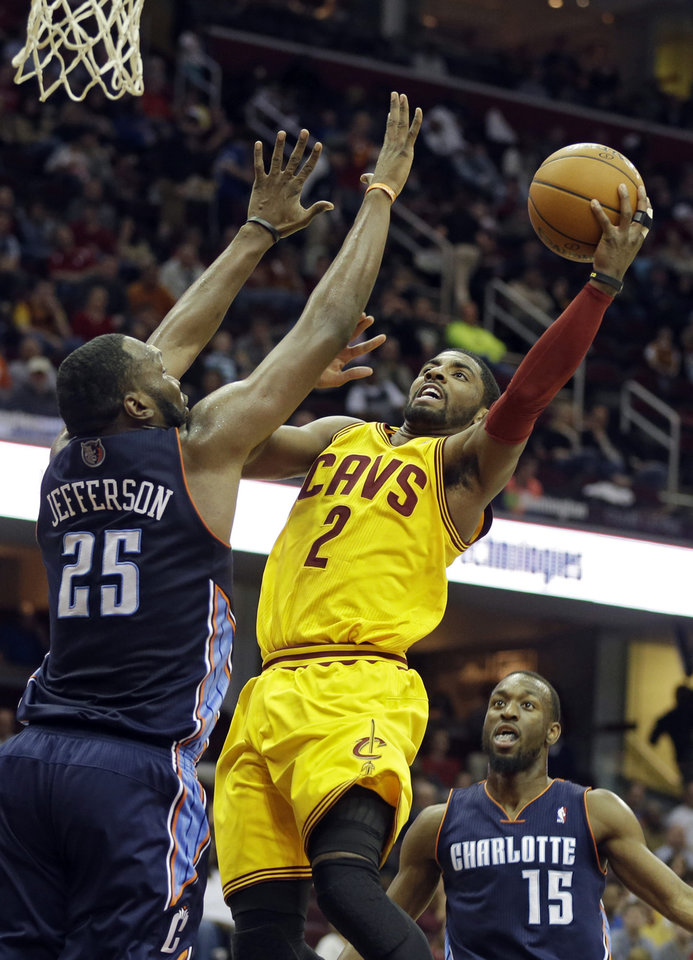 Photo - Cleveland Cavaliers' Kyrie Irving (2) shoots against Charlotte Bobcats' Al Jefferson (25) in the second quarter of an NBA basketball game on Saturday, April 5, 2014, in Cleveland. (AP Photo/Mark Duncan)