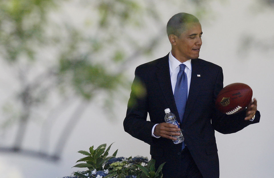 Photo - FILE - In this  Thursday, May 21, 2009,  file photo, President Barack Obama plays with a football as he walks back to the Oval Office of the White House in Washington. Concerned that too little is known about the effects of head injuries in young athletes, President Barack Obama is bringing representatives of professional sports leagues, coaches, parents, youth sports players, researchers and others to the White House Thursday, May 29, 2014, to help educate the public about youth sports concussions. (AP Photo/Charles Dharapak, File)