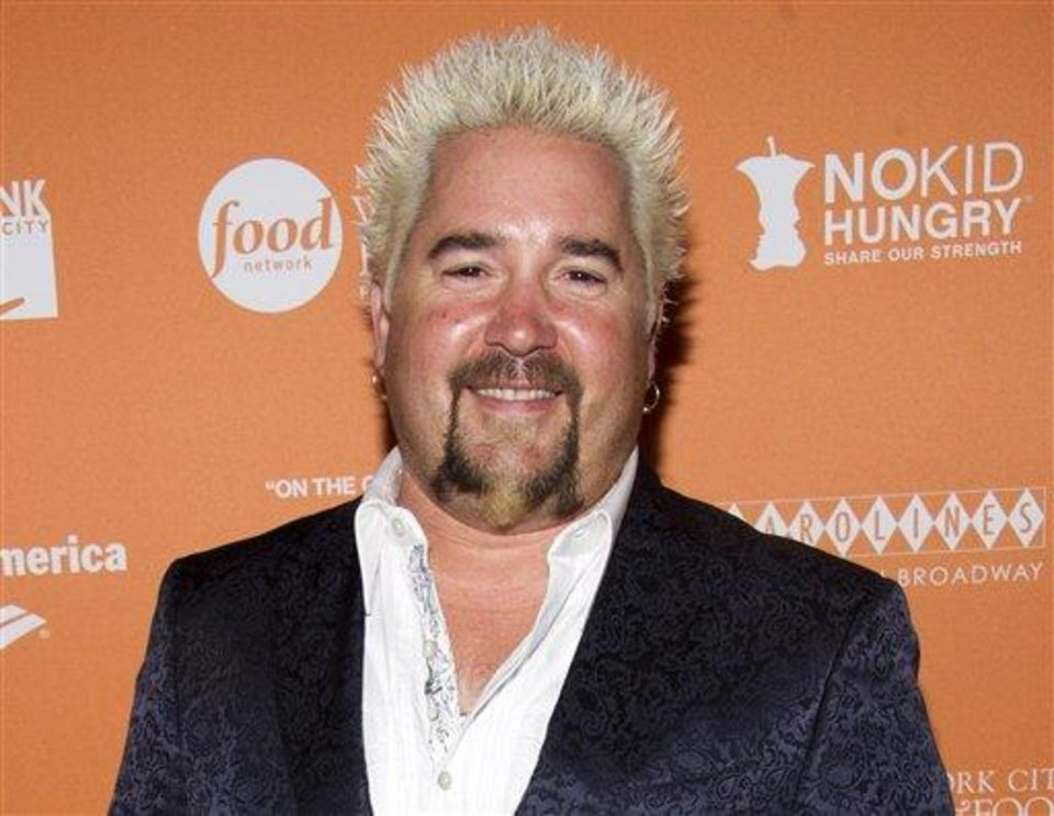 "FILE - This Oct. 11, 2012 file photo shows chef Guy Fieri at the ""On The Chopping Block: A Roast of Anthony Bourdain"" in New York. New York Times reviewer Pete Wells scored a celeb smack down when he dissed Fieri's New York restaurant, Guy's American Kitchen & Bar, in a scathing 1,000-word review written entirely in questions. Wells took heat for beating on Food Network's bad boy, but the review, which tore across Twitter the instant it was posted, certainly drove hordes to Fieri's tables, even if only to rubberneck the culinary accident. (Photo by Charles Sykes/Invision/AP, File)"