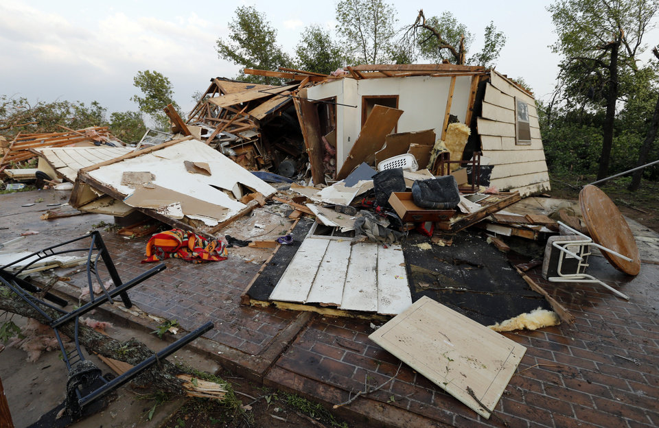 Photo - Levi Littlecreek and girlfriend Sharon Ponkilla were trapped inside this home after a tornado struck near 156th street and Franklin Road on Sunday, May 19, 2013  in Norman, Okla. Littlecreek used a cell phone to call his brother Andy Warrior who arrived with emergency personnell to extract the couple.  Both were taken to a hospital by ambulance.  Photo by Steve Sisney, The Oklahoman