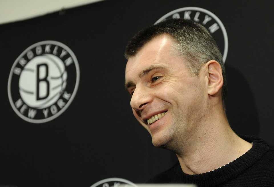 Photo - Brooklyn Nets principal owner Mikhail Prokhorov smiles as he speaks to the media concerning the firing of head coach Avery Johnson.  Prokhorov spoke at half time of an NBA basketball game against the Charlotte Bobcats on Friday, Dec., 28, 2012 at Barclays Center in New York. (AP Photo/Kathy Kmonicek)