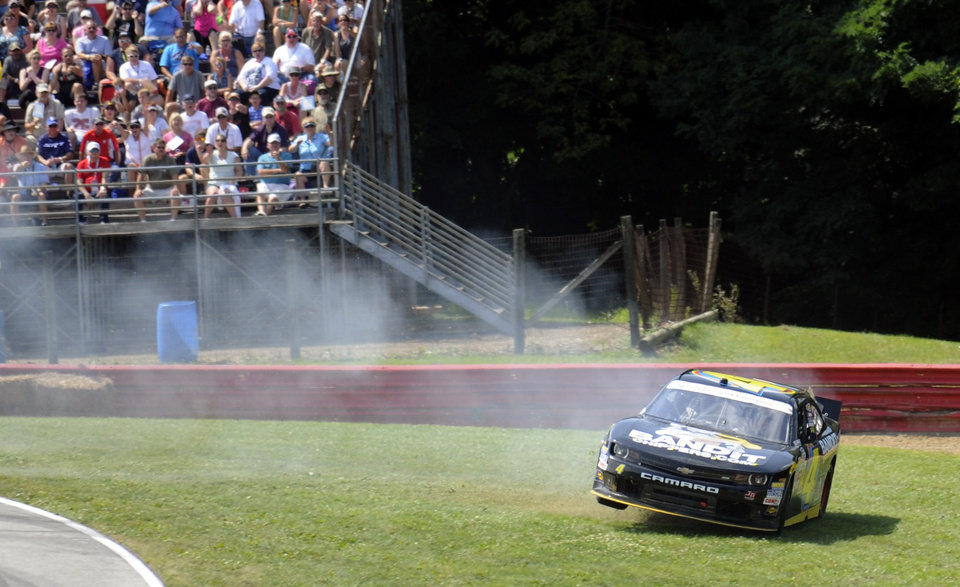 Photo - Jeffrey Earnhardt slides off course in Turn 4 during the NASCAR Nationwide Series Nationwide Children's Hospital 200 auto race at Mid-Ohio Sports Car Course Saturday, Aug. 16, 2014, in Lexington, Ohio. (AP Photo/Tom E. Puskar)