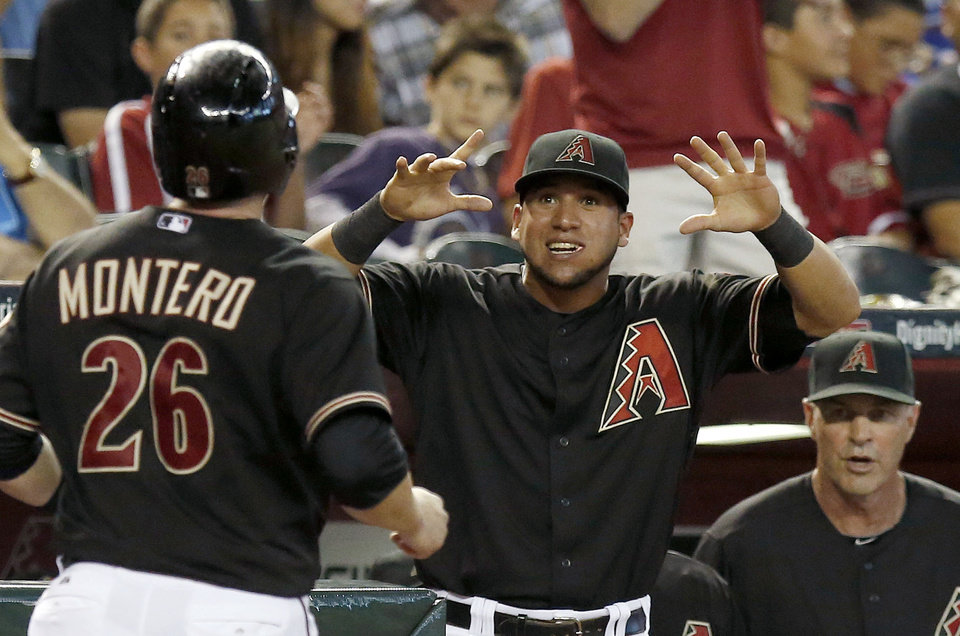 Photo - Arizona Diamondbacks' Miguel Montero (26) celebrates his run scored against the Chicago Cubs with teammate David Peralta, middle, and manager Kirk Gibson, right, during the fifth inning of a baseball game on Saturday, July 19, 2014, in Phoenix.  Montero had a 3-run double when he batted in the fifth inning. (AP Photo/Ross D. Franklin)