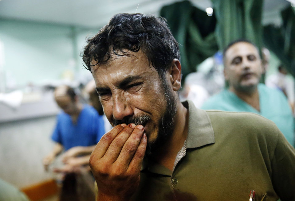 Photo - A Palestinian man cries after bringing a child, wounded in an Israeli strike on a compound housing a U.N. school in Beit Hanoun, in the northern Gaza Strip, to the emergency room room of the Kamal Adwan hospital in Beit Lahiya, Thursday, July 24, 2014. Israeli tank shells hit the compound, killing more than a dozen people and wounding dozens more who were seeking shelter from fierce clashes on the streets outside. Gaza health official Ashraf al-Kidra says the dead and injured in the school compound were among hundreds of people seeking shelter from heavy fighting in the area. (AP Photo/Lefteris Pitarakis)
