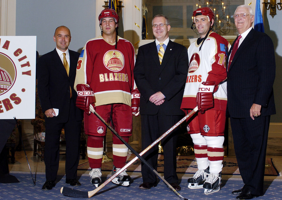 Photo - OKLAHOMA CITY, OK, THURSDAY, 8/26/04; BLAZERS UNVEIL NEW LOOK; LOGO, CHANGE, CHL HOCKEY:  Oklahoma City Blazers co-captains Tyler Fleck (second from left) and Hardy Sauter (second from right) model the newly-designed Blazer uniforms while standing with Brad Lund, Express Sports CEO, Governor Brad Henry and Blazer owner Bob Funk..  Fleck models the away-game uniform, while Sauter models the home-game uniform    Staff photo by Roger Klock.
