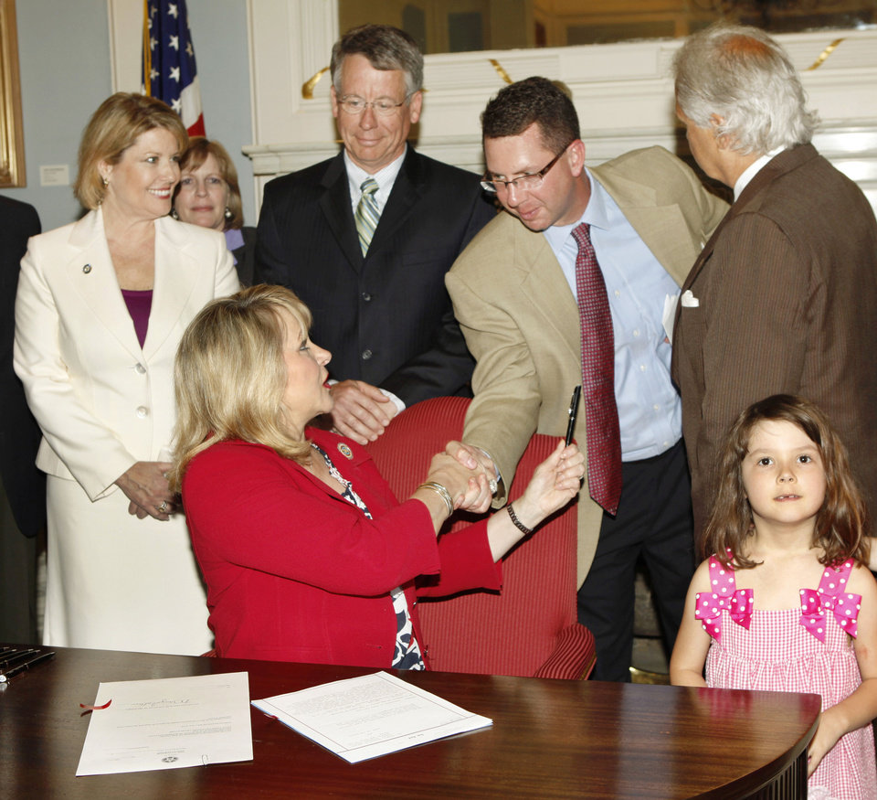 Photo - Gov. Mary Fallin shakes hands and gives the pen to House Speaker Kris Steele, R-Shawnee, after signing legislation Thursday that restructures the organization of the Department of Human Services.  Photo by Jim Beckel, The Oklahoman
