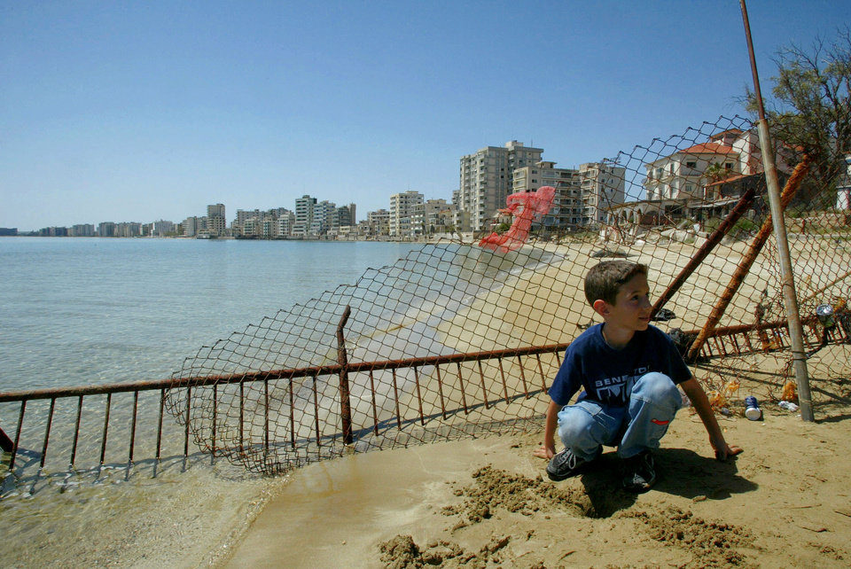 Photo - FILE - In this Monday, May 5, 2003 file photo, a Greek Cypriot boy sits on a beach in front of deserted hotels in an area used by the Turkish military, seen in distance, in the Turkish-occupied abandoned coastal city of Varosha, in southeast of island of Cyprus. Time virtually stopped in 1974 for the Mediterranean tourist playground of Varosha. When Turkey invaded Cyprus in the wake of a coup by supporters of union with Greece, thousands of residents fled, and chain-link fences enclosed a glamorous resort that it's said once played host to Hollywood royalty like Elizabeth Taylor.    (AP Photo/Petros Karadjias, file)
