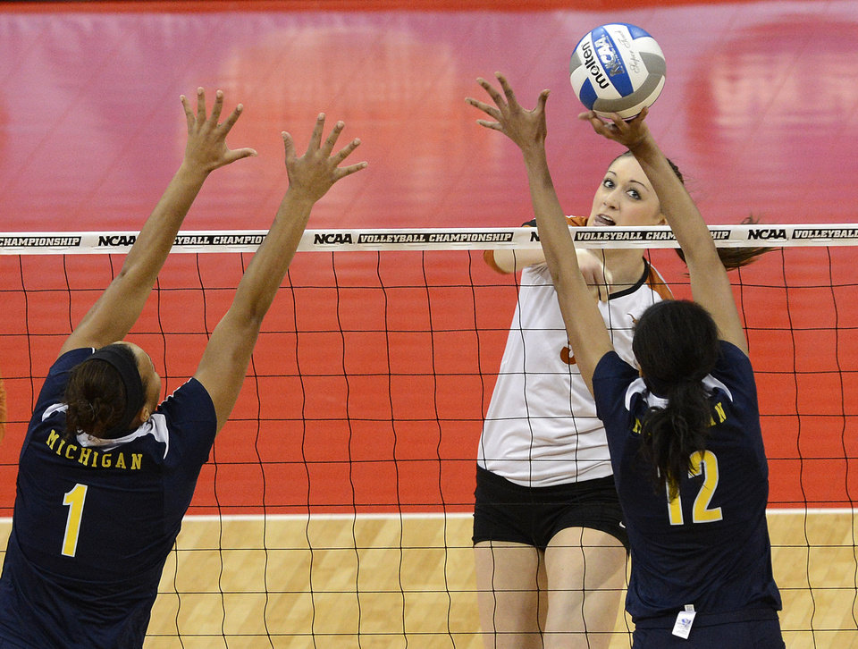 Photo - Texas' Molly McCage, facing, attempts to spike the ball past the defense of Michigan's Krystalyn Goode, right, and Molly Toon during the national semifinals of the NCAA college women's volleyball tournament Thursday, Dec. 13, 2012 in Louisville, Ky. (AP Photo/Timothy D. Easley)
