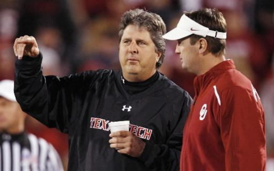 Photo - Texas Tech head  coach Mike Leach, left, and OU head  coach Bob Stoops talk before the college football game between the University of Oklahoma Sooners and Texas Tech University at Gaylord Family -- Oklahoma Memorial Stadium in Norman, Okla., Saturday, Nov. 22, 2008. BY NATE BILLINGS