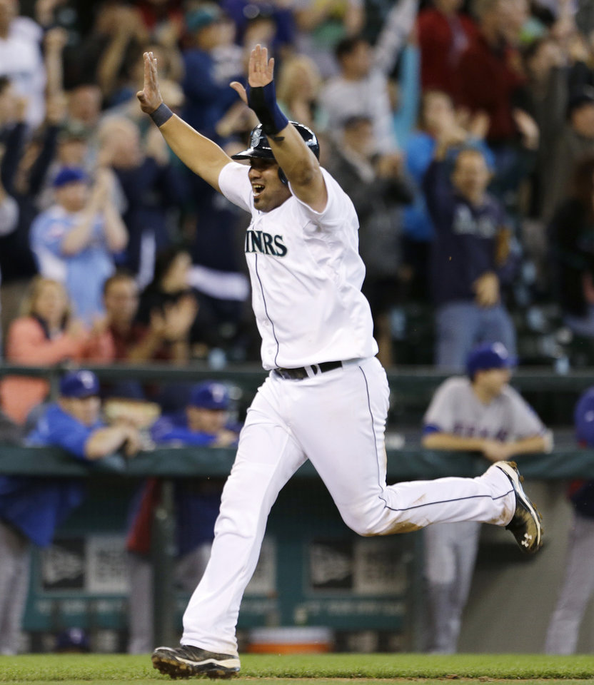 Seattle Mariners\' Kendrys Morales raises his arms as he heads home with the winning run against the Texas Rangers in the 13th inning in a baseball game on Sunday, May 26, 2013, in Seattle. The Mariners won 4-3 on a single by Jason Bay. (AP Photo/Elaine Thompson)