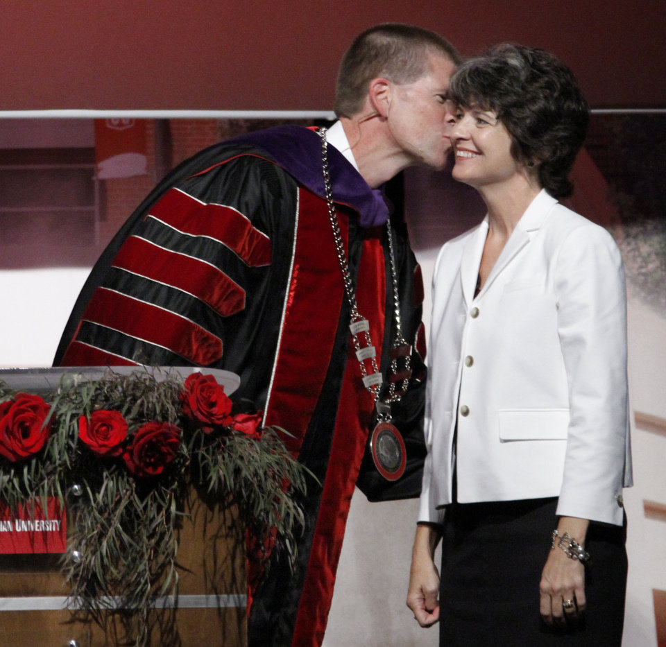Photo - President of Oklahoma Christian University John deSteiguer, kisses his wife, Darla during his inauguration in Oklahoma City, Monday August 27, 2012. Photo By Steve Gooch, The Oklahoman