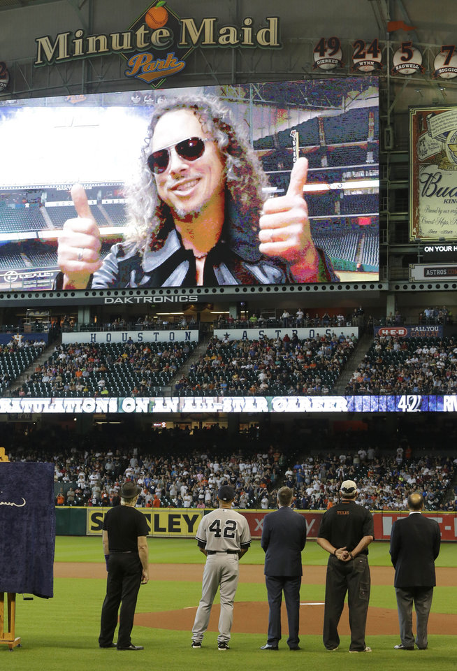 Photo - New York Yankees relief pitcher Mariano Rivera (42) and others watch as Kirk Hammett of the band Metallica gives him a thumbs-up on the big screen during a presentation before a baseball game against the Houston Astros Sunday, Sept. 29, 2013, in Houston. Rivera is retiring after 18 years in baseball. (AP Photo/Richard Carson)