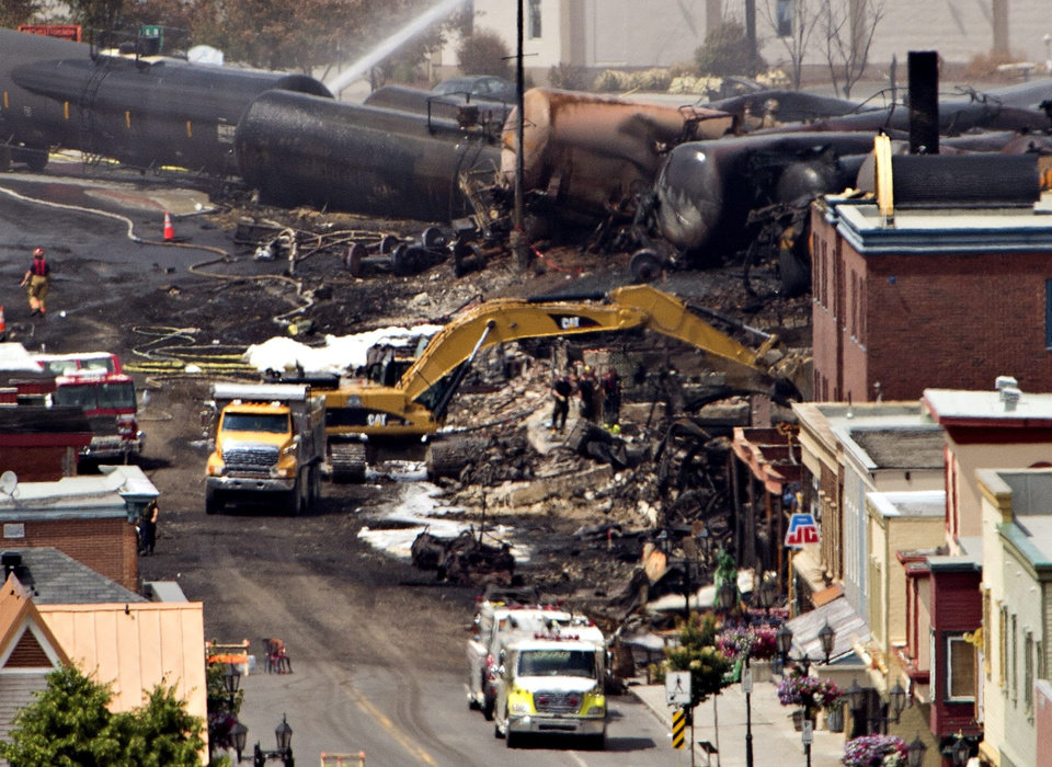 Photo - Searchers dig through the rubble for victims of the inferno in Lac-Megantic, Quebec, Monday, July 8, 2013. A runaway train derailed early Saturday igniting tanker cars carrying crude oil.  (AP Photo/THE CANADIAN PRESS,Ryan Remiorz)