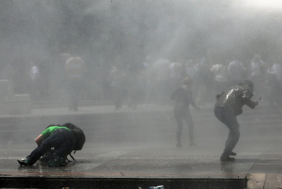 Photo - A news cameraman, left, falls on the ground as Turkish riot police spray water cannon at demonstrators who remained defiant after authorities evicted activists from an Istanbul park, making clear they are taking a hardline against attempts to rekindle protests that have shaken the country, in city's main Kizilay Square in Ankara, Turkey, Sunday, June 16, 2013. (AP Photo/Burhan Ozbilici)