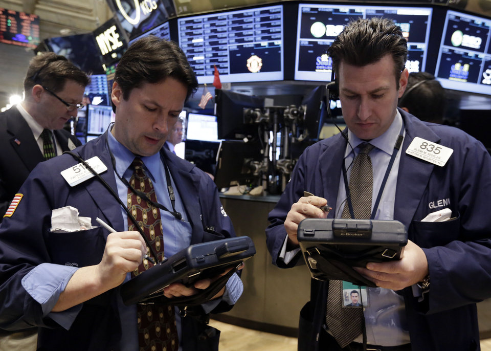 Trader Patrick McKeon, and Glenn Kessler, foreground left and right, work on the floor of the New York Stock Exchange Monday, March 17, 2014. Stocks are sharply higher in early trading following news that output at U.S. factories surged last month. (AP Photo/Richard Drew)