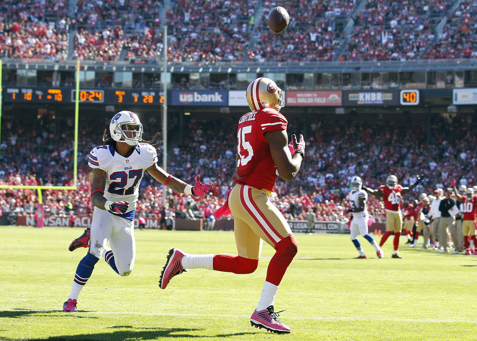 San Francisco 49ers wide receiver Michael Crabtree (15) catches a touchdown pass from quarterback Alex Smith in front of Buffalo Bills cornerback Stephon Gilmore (27) during the second quarter of an NFL football game in San Francisco, Sunday, Oct. 7, 2012. (AP Photo/Tony Avelar)