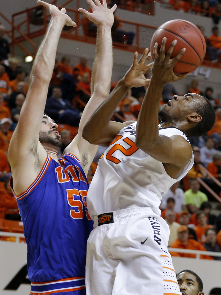 Photo - Oklahoma State's Markel Brown (22) goes to the basket beside Texas-Arlington's Jordan Reves (55) during a college basketball game between Oklahoma State University and UT Arlington at Gallagher-Iba Arena in Stillwater, Okla., Wednesday, Dec. 19, 2012. Photo by Bryan Terry, The Oklahoman