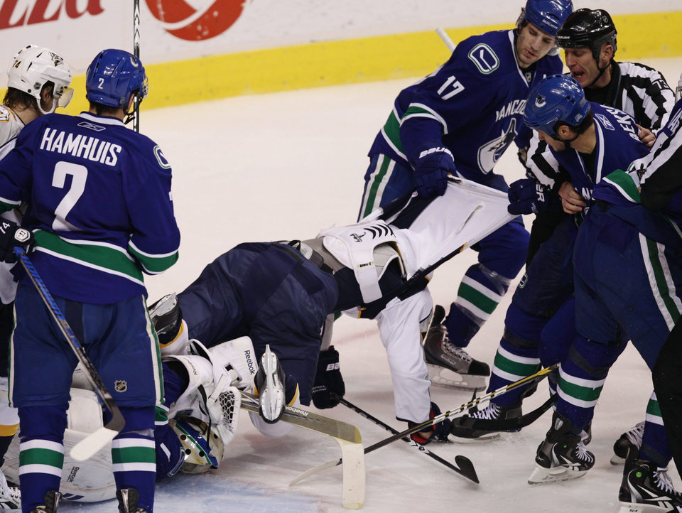 Photo -   Vancouver Canucks' Ryan Kesler, 17, and Kevin Bieksa, right, pull Nashville Predators' Patric Hornqvist, center, of Sweden, off Canucks' goalie Roberto Luongo during the second period of an NHL hockey game in Vancouver, Canada, on Wednesday Jan. 26, 2011. (AP Photo/The Canadian Press, Darryl Dyck)