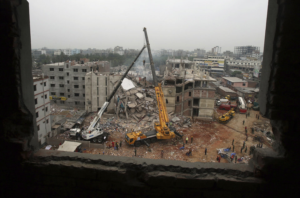 The garment factory building collapsed on Wednesday, is framed by a window from nearby as a crane prepares to lift its fallen ceiling, in Savar, near Dhaka, Bangladesh, Monday April 29, 2013. Rescue workers in Bangladesh gave up hopes of finding any more survivors in the remains of a building that collapsed five days ago, and began using heavy machinery on Monday to dislodge the rubble and look for bodies - mostly of workers in garment factories there. At least 381 people were killed when the illegally constructed, 8-story Rana Plaza collapsed in a heap on Wednesday morning along with thousands of workers in the five garment factories in the building.(AP Photo/Wong Maye-E)