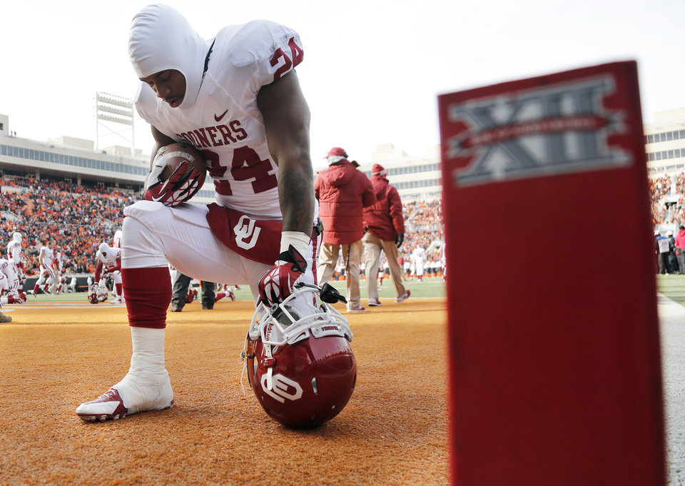 Photo - Oklahoma's Brennan Clay (24) says a prayer before the start of the Bedlam college football game between the Oklahoma State University Cowboys (OSU) and the University of Oklahoma Sooners (OU) at Boone Pickens Stadium in Stillwater, Okla., Saturday, Dec. 7, 2013. Photo by Chris Landsberger, The Oklahoman