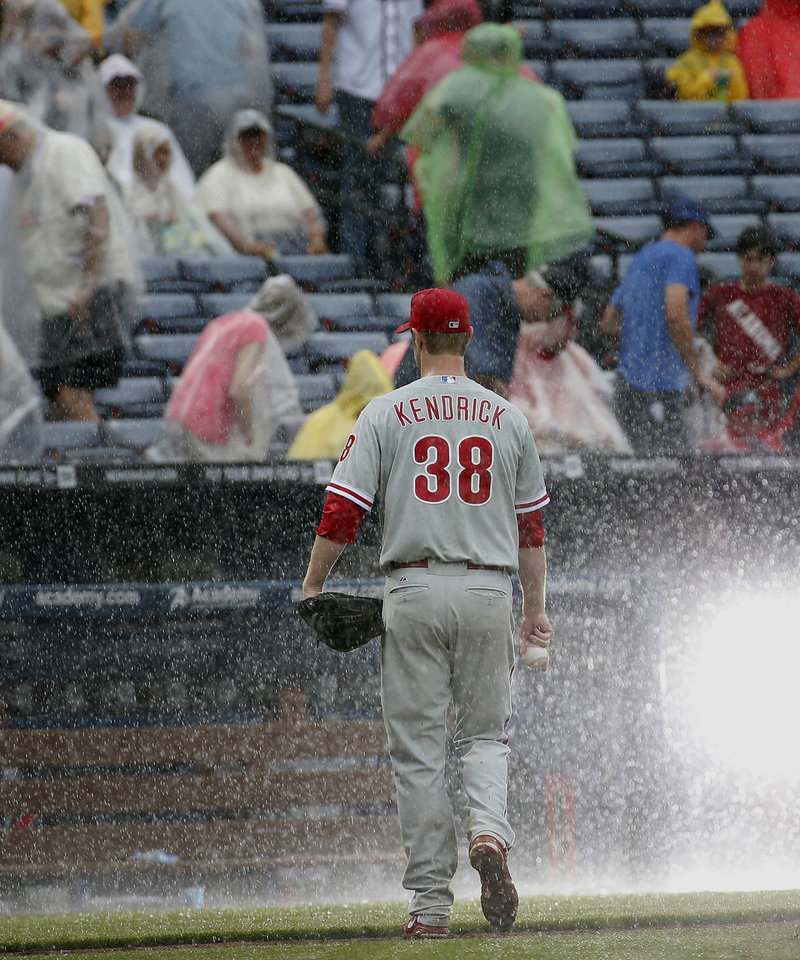 Photo - Philadelphia Phillies starting pitcher Kyle Kendrick (38) leaves the field as play is stopped for rain during the sixth inning of a baseball game against the Atlanta Braves in Atlanta, Sunday, July 20, 2014. (AP Photo/John Bazemore)