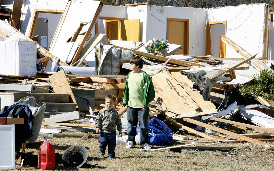 Mark Graham, 2, and Deric Brawley, 12, looking at a neighbor's damaged home on Newport Road in Lone Grove, Wednesday, Feb. 11, 2009. BY PAUL B. SOUTHERLAND, THE OKLAHOMAN