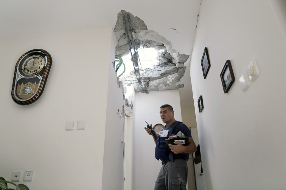An Israeli police officer stands inside a damaged house after a rocket fired by Palestinian militants from Gaza Strip landed in Ashkelon, southern Israel, Sunday, Nov. 18, 2012. Israel launched the operation last Wednesday by assassinating Hamas� military chief and carrying out dozens of airstrikes on rocket launchers and weapons storage sites. Over the weekend, the operation began to target Hamas government installations as well, including the offices of its prime minister. (AP Photo/Tsafrir Abayov)