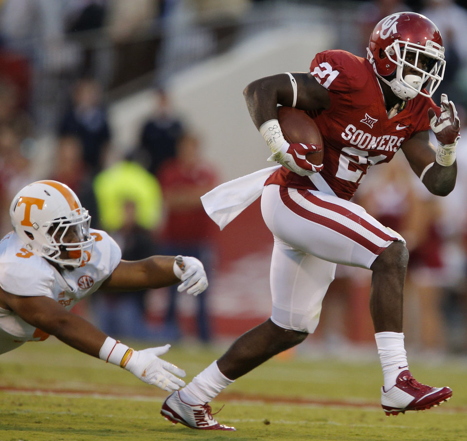 Photo - Oklahoma's Keith Ford (21) runs past Tennessee's Derek Barnett (9)during a college football game between the University of Oklahoma Sooners (OU) and the Tennessee Volunteers at Gaylord Family-Oklahoma Memorial Stadium in Norman, Okla., on Saturday, Sept. 13, 2014. Photo by Bryan Terry, The Oklahoman