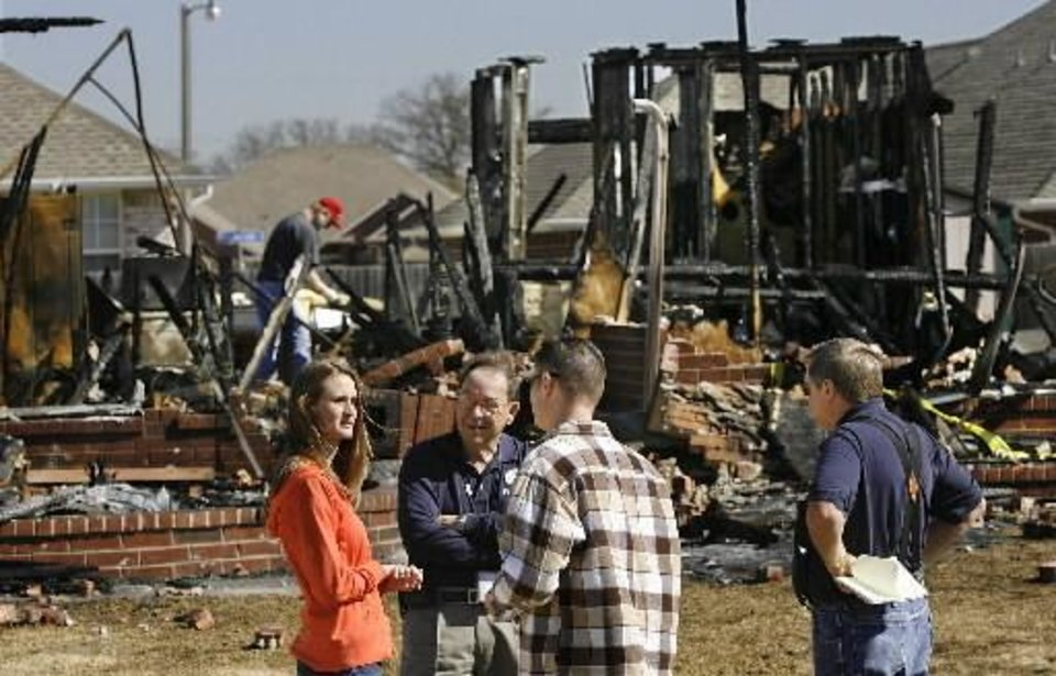 Winston Barton, center, talks to Valerie and Matt Waxenfelter in front of a destroyed home in the Oakwood East Royale neighborhood Tuesday morning. By Jim Beckel.