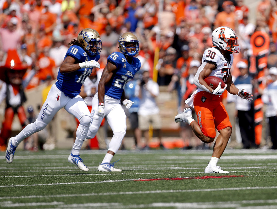 Photo - Oklahoma State's Chuba Hubbard (30) rushes for a touchdown as Tulsa's Manny Bunch (10) and Akayleb Evans (26) chase him in the first quarter during a college football game between the Oklahoma State University Cowboys (OSU) and the University of Tulsa Golden Hurricane (TU) at H.A. Chapman Stadium in Tulsa, Okla., Saturday, Sept. 14, 2019. [Sarah Phipps/The Oklahoman]