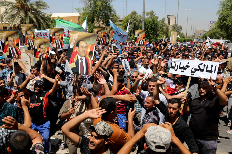 Photo - Pro-government supporters of Prime Minister Nouri al-Maliki, chant slogans during a demonstration in Baghdad, Iraq, Wednesday, Aug 13, 2014. Tanks and Humvees were positioned on Baghdad bridges and at major intersections on Wednesday, with security personnel more visible than usual as pro-Maliki demonstrators took to Firdous Square in the capital, pledging their allegiance to him. Arabic on the placard at right reads,