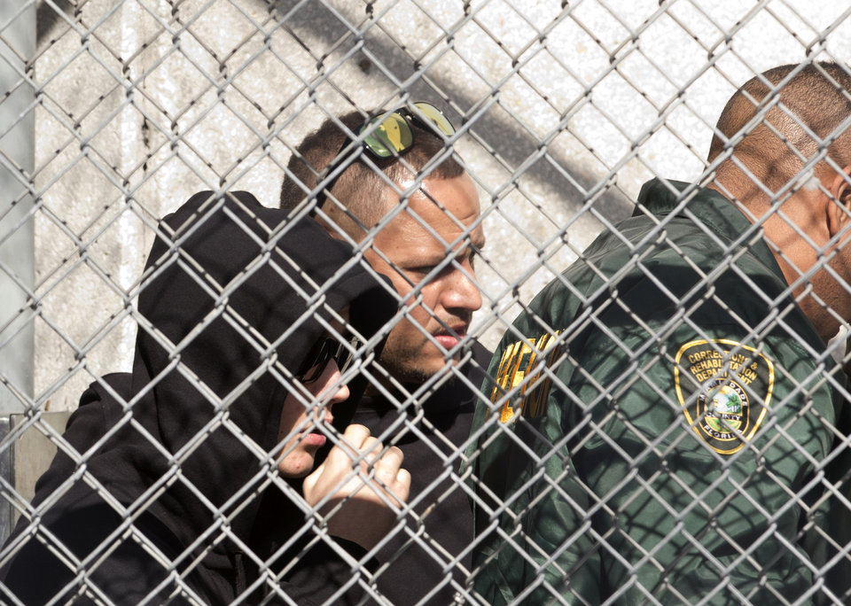 Photo - Pop singer Justin Bieber, left, is escorted out of the Turner Guilford Knight Correctional Center, Thursday Jan. 23, 2014 in Doral, Fla., following his arrest earlier in the day in Miami Beach. Bieber was arrested and charged with driving under the influence and resisting arrest after police said they saw him speeding down a residential street in a yellow Lamborghini. Officers say he had an expired license, was initially not cooperative when he was pulled over, and smelled of alcohol. (AP Photo/Wilfredo Lee)