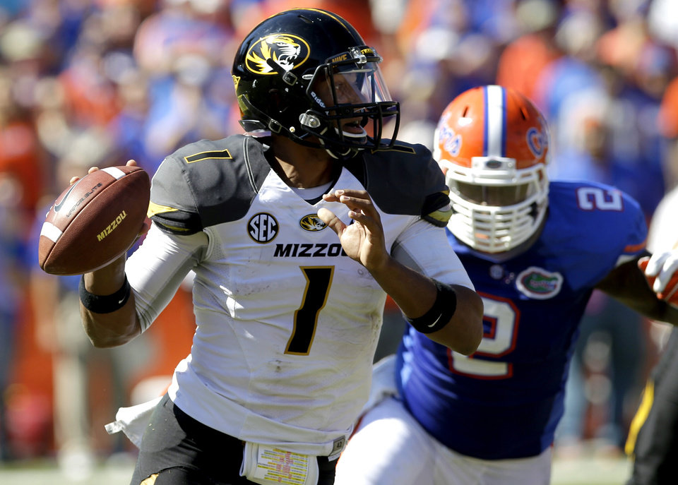 Missouri quarterback James Franklin (1) looks for a receiver as he scrambles away from Florida defensive lineman Dominique Easley (2) during the first half of an NCAA college football game, Saturday, Nov. 3, 2012, in Gainesville, Fla. (AP Photo/John Raoux)