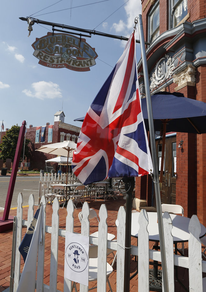 Photo - In this Sept. 5, 2013, photo a British flag hangs outside the Bluebell Saloon and Restaurant in Guthrie,, Okla. The population of the small Oklahoma town is expected to quadruple this weekend as people come to watch the British folk rock band on the second stop of the Mumford & SonsÂ' Gentlemen of the Road concert series in Guthrie. (AP Photo/Sue Ogrocki) ORG XMIT: OKSO104