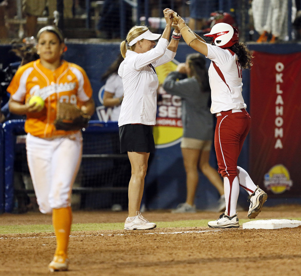 Photo - OU head coach Patty Gasso celebrates with Callie Parsons (12) after Parsons drove in the game-tying run in the eleventh inning during Game 1 of the Women's College World Series NCAA softball championship series between Oklahoma and Tennessee at ASA Hall of Fame Stadium in Oklahoma City, Monday, June 3, 2013. OU won 5-3 in 12 innings. Photo by Nate Billings, The Oklahoman