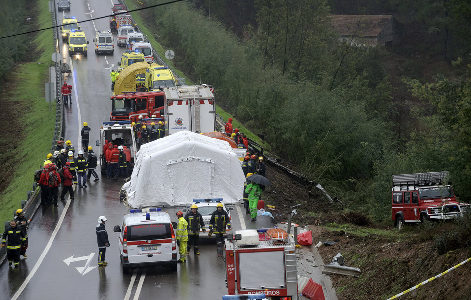 Photo - Portuguese emergency personnel work near the site of a bus crash which killed 10 people and injured 33 in Serta, central Portugal, Sunday, Jan. 27, 2013. National Civil Protection authority spokesman Carlos Guerra says the injured have been taken to hospitals in the cities of Coimbra and Castelo Branco. (AP Photo/Sergio Azenha) PORTUGAL OUT