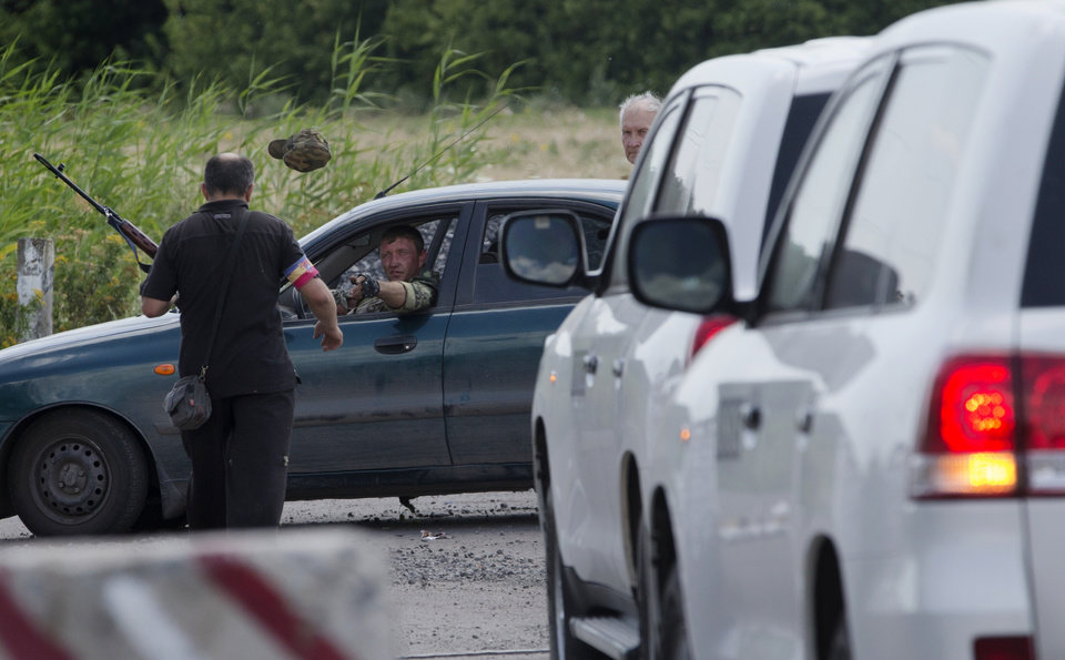 Photo - A pro-Russian rebel throws a hat to his comrade to keep uniform formality as the convoy of the OSCE mission in Ukraine approaches to a check-point near the village of Rassipne, near the scene of the Malaysia Airlines plane crash, Donetsk region, eastern Ukraine, Thursday, July 31, 2014. (AP Photo/Dmitry Lovetsky)