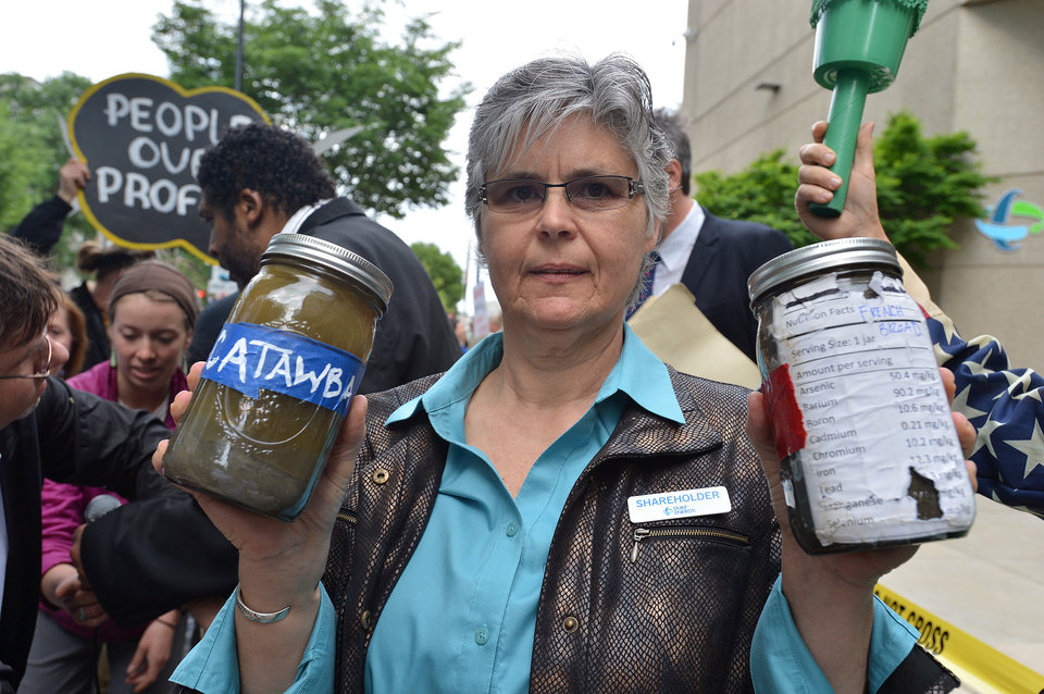 Photo - Duke Energy shareholder Donna Lisenby holds two jars of coals ash from the Catawba and French Broad rivers, as she demonstrates with other protesters Thursday, May 1, 2014, before going into the annual shareholders meeting in Charlotte, N.C.  Some Duke Energy investors plan to push the utility's board of directors to investigate issues surrounding a massive coal ash spill that dumped toxic sludge into a 70-mile stretch of a North Carolina river. (AP Photo/The Charlotte Observer, T. Ortega Gaines) MAGS OUT; TV OUT; NEWSPAPER INTERNET ONLY (REV-SHARE)