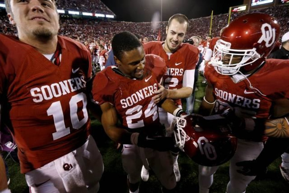Oklahoma's Landry Jones (12) celebrates with Oklahoma's Brennan Clay (24) after winning Bedlam on Saturday, Nov. 24, 2012. Oklahoma won 51-48. Photo by Bryan Terry, The Oklahoman
