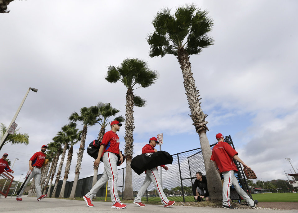 Photo - Philadelphia Phillies players walk to the field for a spring training baseball practice Thursday, Feb. 13, 2014, in Clearwater, Fla. (AP Photo/Charlie Neibergall)