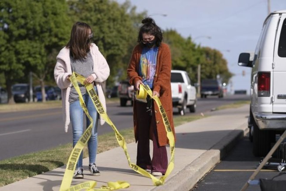 Photo -  Two crew members wrangle crime scene tape on Oct. 15 on the set of the Oklahoma film
