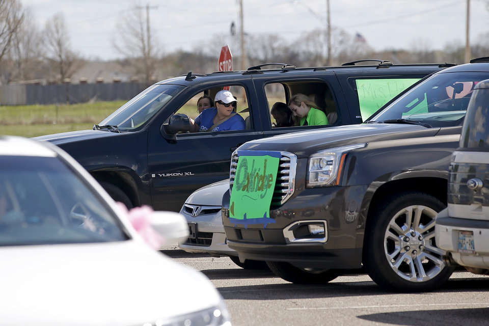 Photo - Vehicle line up at Oakridge Elementary before starting a faculty caravan through neighborhoods around the Moore school, Tuesday, March 24, 2020. [Bryan Terry/The Oklahoman]