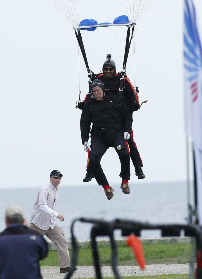 Photo - Former President George H.W. Bush, strapped to Sgt. 1st Class Mike Elliott, a retired member of the Army's Golden Knights parachute team, prepare to land on the lawn at St. Anne's Episcopal Church while celebrating Bush's 90th birthday in Kennebunkport, Maine, Thursday, June 12, 2014. (AP Photo/Robert F. Bukaty)
