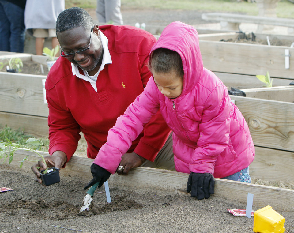 Pastor Theodis Manning assists seven year old Destiny Stokeley in planting a vegetable plant at the Oklahoma County Social Services in NE Oklahoma City, OK, Saturday, April 13, 2013,  By Paul Hellstern, The Oklahoman