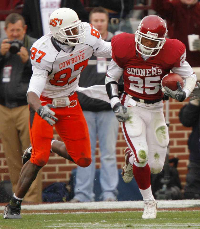 Photo - Oklahoma's D.J. Wolfe (25) takes a fumble recovery up filed past Oklahoma State's Brandon Pettigrew (87) during the first half of the college football game between the University of Oklahoma Sooners (OU) and the Oklahoma State University Cowboys (OSU) at the Gaylord Family-Memorial Stadium on Saturday, Nov. 24, 2007, in Norman, Okla. 