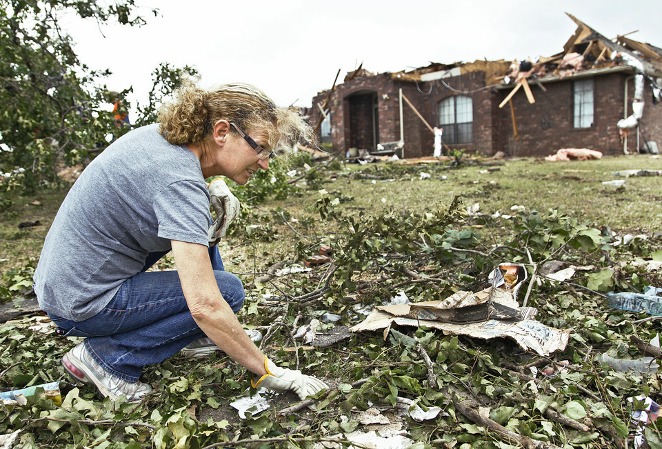 Photo - Above and right: Donna Hensley gathers personal belongings scattered in the debris Wednesday. Hensleys home was destroyed by a tornado Monday.