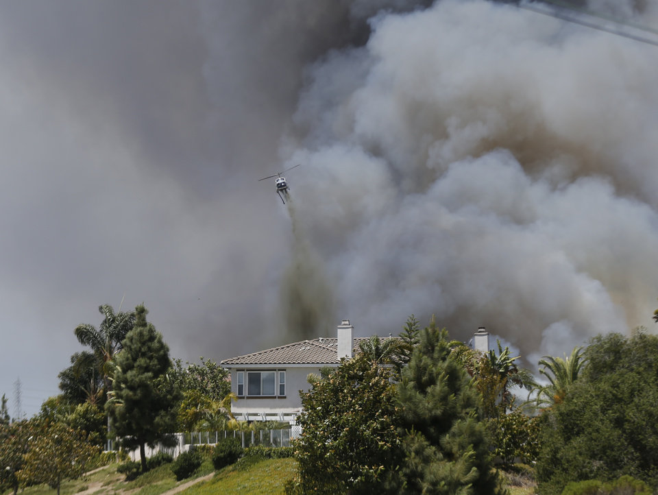 Photo - A helicopter drops fire fighting material over a house as smoke envelopes the area  Wednesday, May 14, 2014, in Carlsbad, Calif.  Weather conditions that at least temporarily calmed allowed firefighters to gain ground early Wednesday on a pair of wildfires that forced thousands of residents to leave their homes. (AP Photo)