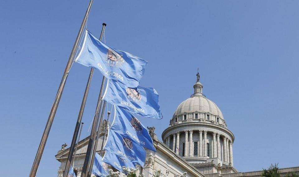 Photo - Flags fly at half-staff at the state Capitol in Oklahoma City, Wednesday, Aug. 26, 2015, in honor of state Labor Commissioner Mark Costello. His body will lie in repose in the rotunda of the state Capitol on Thursday, Aug. 26, 2015. (AP Photo/Sue Ogrocki)
